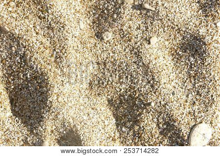 Sea Sand Background Texture, Top View, Shadow On The Sand Stone In The Sand