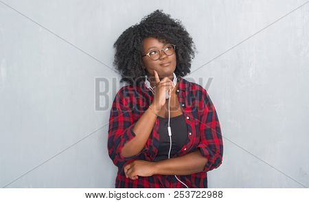 Young african american woman over grey grunge wall wearing headphones with hand on chin thinking about question, pensive expression. Smiling with thoughtful face. Doubt concept.