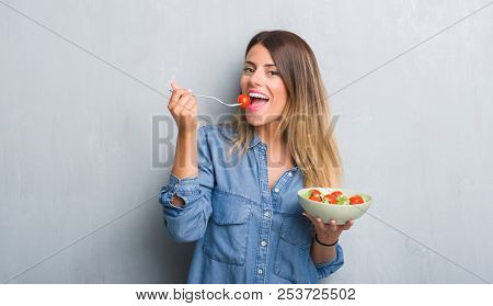 Young adult woman over grey grunge wall eating healthy tomato salad with a happy face standing and smiling with a confident smile showing teeth