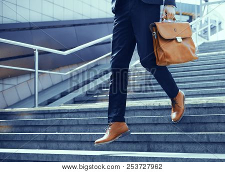 Businessman Making Steps Down Stairs. Cropped Shot Of Man Wearing Elegant Suit And Shoes Walking Dow