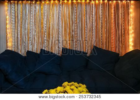Comfortable Navy Blue Sofa In Living Room With Flowers In Front And Yellow Led Decorative Lights On