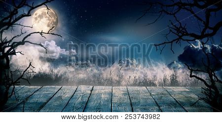Scary horror background with empty wooden deck, ready for product placement. Halloween spooky background.
