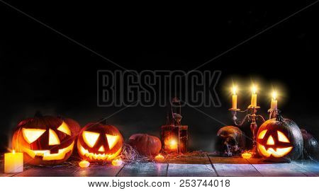 Scary horror background with halloween pumpkins jack o lantern, placed on wooden deck. Halloween spooky background isolated on black