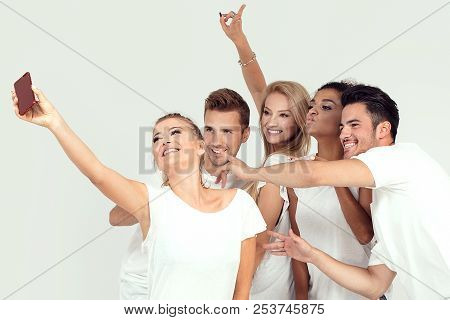 Group Of Young Smiling People Taking Selfie.