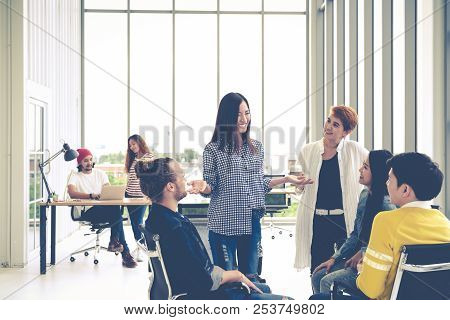 Group Of Young Multiethnic Creative Team Engaged Brainstorm In Small Meeting While Standing, Sitting
