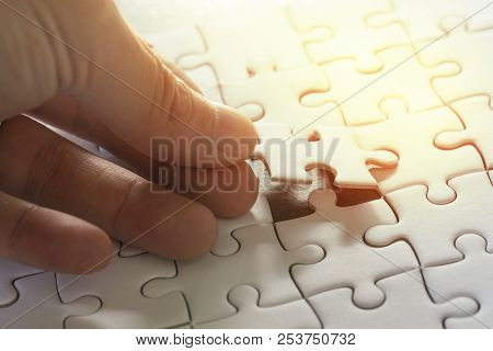 poster of Business strategy, finish or finalize, problem solution metaphor concept, man holding last piece of jigsaw puzzle putting to complete the perfect game.