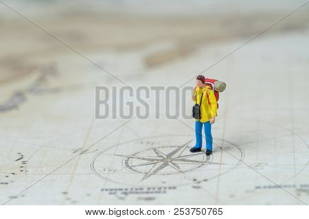 Miniature people young man backpacker standing on vintage world map with compass, Travel, tourism, vacation or wanderlust life concept, plan for next destination, new adventure journey. poster