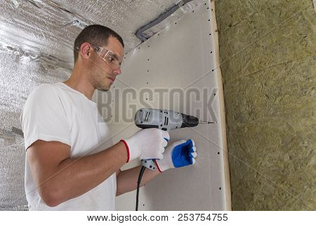 Worker In Goggles With Screwdriver Working On Insulation. Drywall On Wall Beams, Insulating Rock Woo