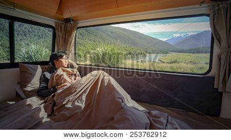 Young Asian Man Staying In The Blanket Looking At Mountain Scenery Through The Window In Camper Van