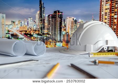 Architectural Drawing Plan With Blueprint Rolls, Safety Helmet And Drawing Tools On Working Table. B