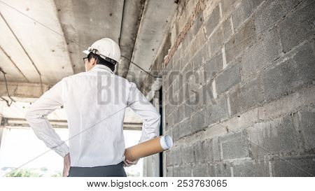 Asian Male Engineer Or Architect Holding Blueprints Or Architectural Drawing While Wearing Protectiv