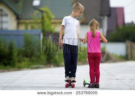 Cute Young Blond Children Girl In Pink Clothing On Scooter And Handsome Boy On Skateboard Playing On