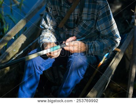 Contrast Outdoor Shot Of A Fisherman With Rod Sitting In A Boat
