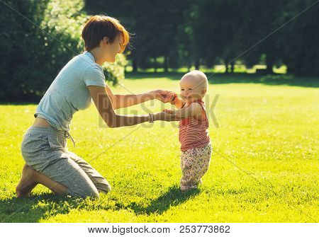 Barefoot Baby Learning To Walk In Summer Park. Young Mother Helps Her Child To Take The First Steps
