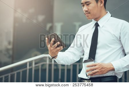 Asian Businessman Holding Tablet And Looking Email In Morning.