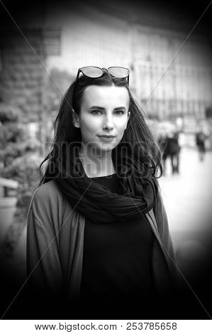 A Black-haired Girl In The City On The Background Of The Avenue, Passers-by, In A Big Black Scarf, G