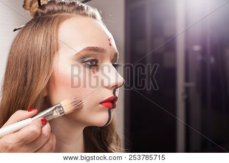 professional make up woman applying foundation on a cheek of a young beautiful model with unusual makeup and a coiffure using a brush. free copyspace poster