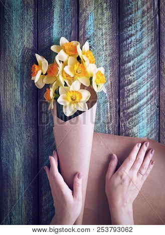 Woman Wrapping Narcissus Bouquet In Brown Paper On Green Wooden Background