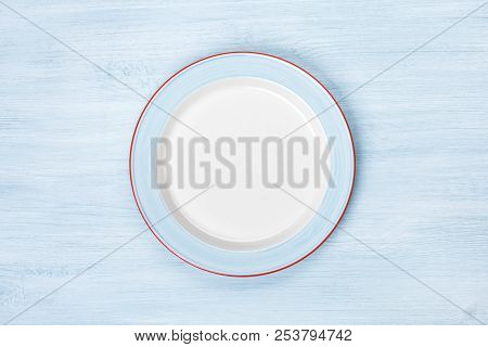Empty Plate On Blue Wooden Table. Top View With Copyspace
