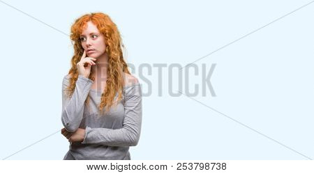 Young redhead woman with hand on chin thinking about question, pensive expression. Smiling with thoughtful face. Doubt concept.