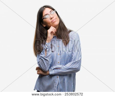 Young beautiful hispanic business woman with hand on chin thinking about question, pensive expression. Smiling with thoughtful face. Doubt concept.
