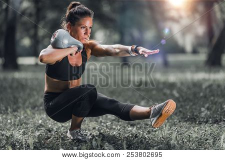 Outdoor Exercising. Female Athlete Exercising With Kettlebell In The Park.