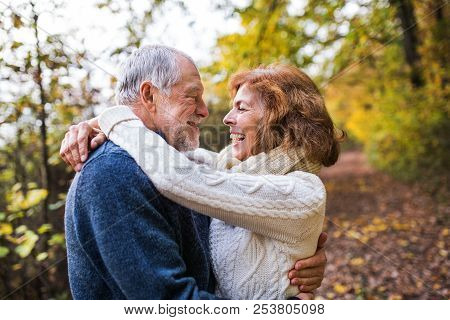 Senior Couple Looking At Each Other In An Autumn Nature, Hugging.