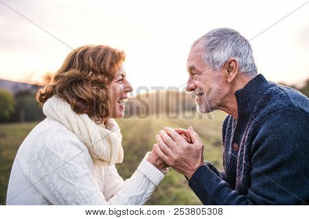 Senior Couple Looking At Each Other In An Autumn Nature, Holding Hands.