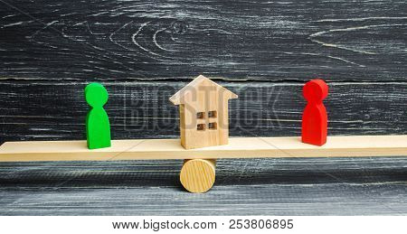 wooden figures on the scales. clarification of ownership of the house, real estate. court. rivals in business. competition. victory and defeat. concept of success and power. Estate law concept. property poster