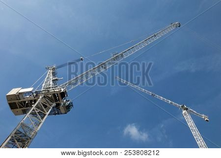 A Perspective View Looking Up At Two Tall White Construction Cranes On A Building Site Against A Blu