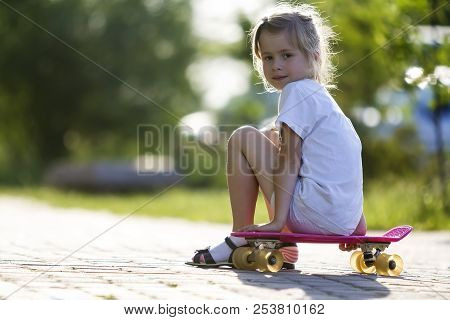 Pretty Cute Little Blond Girl In White Shorts And T-shirt Sitting On Pink Skateboard And Smiling In