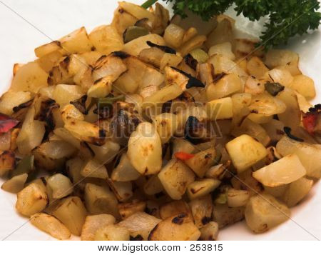 a very close view of some hash brown potatoes o'brien with a sprig of parsley. poster