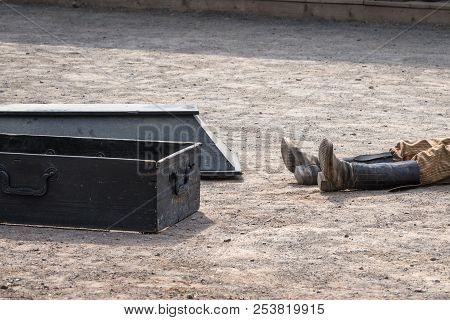 Coffin Next To A Dead Man With His Boots On A Dirt Road In A Wild West City