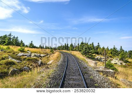 Railroad Track Curving To The Left In Nature With Pine Trees And Rocks Under A Blue Sky