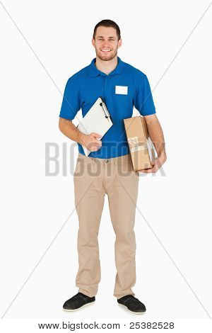 Smiling young salesman with clipboard and parcel against a white background