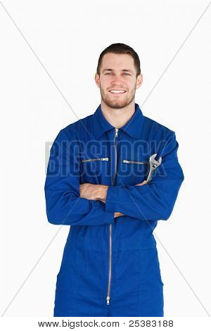 Smiling young mechanic in boiler suit with wrench and arms folded against a white background