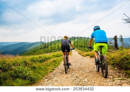 Cycling, mountain biker couple on cycle trail in autumn Mountains. Man and woman cycling MTB flow trail.