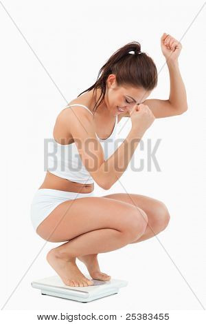 Portrait of a happy woman squatting on scales against a white background