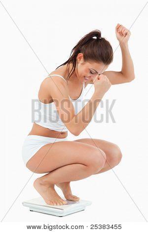 Porträt einer glücklichen Frau hockt auf Skalen vor einem weißen Hintergrund
