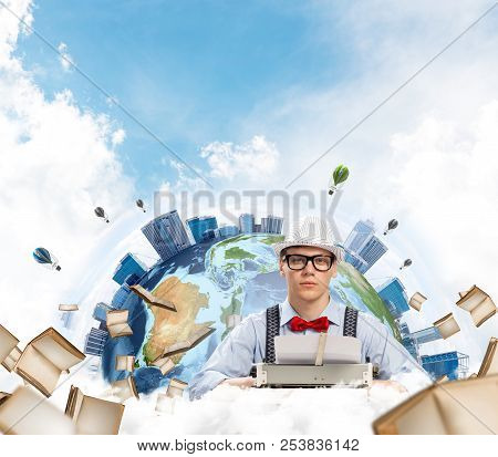 Young man writer in hat and eyeglasses using typing machine while sitting at the table with flying books and Earth globe among cloudy skyscape on background. Elements of this image furnished by NASA poster