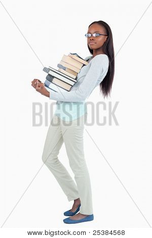 Side view of young woman carrying a pile of books against a white background