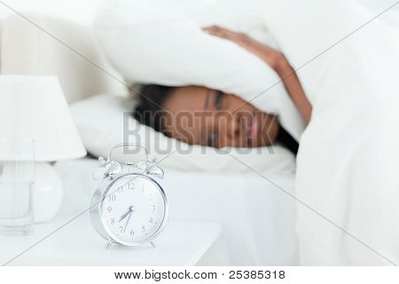 Young woman covering her ears while her alarm clock is ringing with the camera focus on the object