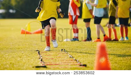 Young Athletes Training With Football Equipment. Football Speed Training For Kids. Young Footballer