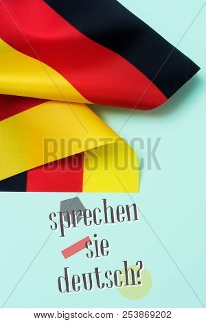 some flags of Germany and the question sprechen sie deutsch? do you speak German? written in German, on a green background poster