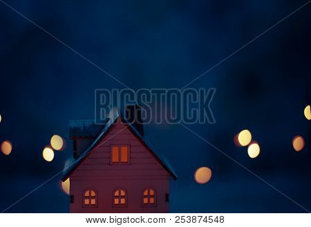 Miniature Christmas Village Scene With Toy Wooden House Windows Lit With Yellow Light With Dark Blue