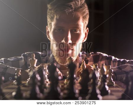 Young Bearded Chess Grandmaster Sitting And Thinking On The Next Move In Dark Room