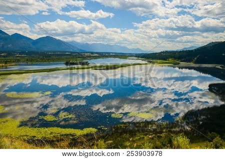 The Sky Reflected In The Columbia Wetlands In A Mountain Landscape Near Invermere, British Columbia,