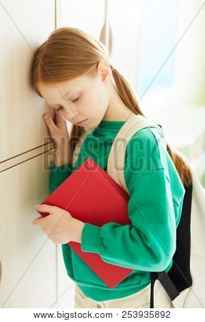 Distraught redhead schoolgirl with ponytails being depressed holding workbook and leaning on wooden lockers, bullying at school concept