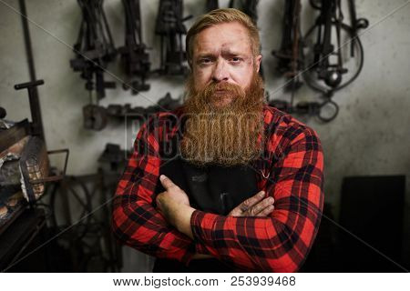 Portrait of serious confident handsome male smith with long beard looking scowling and crossing arms on chest in workshop poster