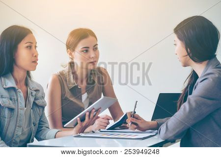 Multicultural businesswomen working group discuss in group meeting at the office. Cooperation of ethnic diversity. poster